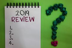 Text sign showing 2019 Review. Conceptual photo seeing important events or actions that made previous year Open notebook crumpled. Papers forming question mark Royalty Free Stock Photo