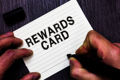 Text sign showing Rewards Card. Conceptual photo Help earn cash points miles from everyday purchase Incentives Man holding marker royalty free stock photo
