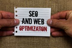 Text sign showing Seo And Web Optimization. Conceptual photo Search Engine Keywording Marketing Strategies Man holding. Piece notebook paper jute background stock images
