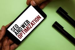 Text sign showing Seo And Web Optimization. Conceptual photo Search Engine Keywording Marketing Strategies Man's hand hold iPhone. With black and red words near royalty free stock photos