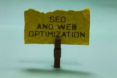 Text sign showing Seo And Web Optimization. Conceptual photo Search Engine Keywording Marketing Strategies Paperclip hold torn yel. Low page written brown words royalty free stock photos