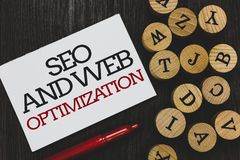 Text sign showing Seo And Web Optimization. Conceptual photo Search Engine Keywording Marketing Strategies Written paper red marke. R beside round woody royalty free stock photo