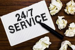 Text sign showing 24 7 Service. Conceptual photo Always available to serve Runs constantly without disruption Marker over notebook. Crumpled papers ripped pages stock photography
