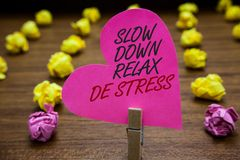 Text sign showing Slow Down Relax De Stress. Conceptual photo Have a break reduce stress levels rest calm Paperclip hold pink hear stock photography