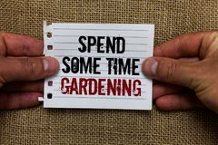 Text sign showing Spend Some Time Gardening. Conceptual photo Relax planting flowers fruits vegetables Natural Man holding piece n. Otebook paper jute background royalty free stock photos