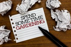 Text sign showing Spend Some Time Gardening. Conceptual photo Relax planting flowers fruits vegetables Natural Paper. Lumps laid randomly around white notepad stock photos