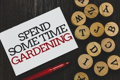 Text sign showing Spend Some Time Gardening. Conceptual photo Relax planting flowers fruits vegetables Natural Written paper red m. Arker beside round woody stock photo