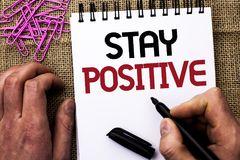 Text sign showing Stay Positive. Conceptual photo Be Optimistic Motivated Good Attitude Inspired Hopeful written by Man Holding Ma. Rker Notebook Book the jute Stock Photos