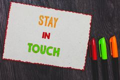 Text sign showing Stay In Touch. Conceptual photo Keep Connected thru Phone Letters Visit Email Social Media White paper red borde. Rs colorful markers wooden stock photo