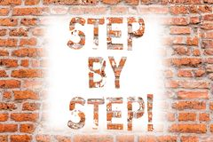 Text sign showing Step By Step. Conceptual photo Slow progress Road to success Direction development Growth Brick Wall art like. Graffiti motivational call stock photography