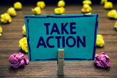 Text sign showing Take Action. Conceptual photo advices someone to do something or reaction right now Clothespin holding blue pape. R note crumpled papers stock photo