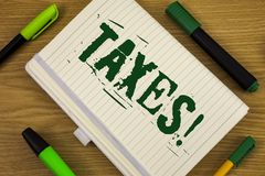 Text sign showing Taxes Motivational Call. Conceptual photo Money demanded by a government for its support written on Notebook Boo. Text sign showing Taxes stock photo