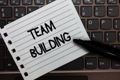 Text sign showing Team Building. Conceptual photo Types of activities used to enhance social relations Notebook piece paper keyboa stock photos