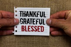 Text sign showing Thankful Grateful Blessed. Conceptual photo Appreciation gratitude good mood attitude Man holding piece notebook. Paper jute background stock photo