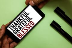 Text sign showing Thankful Grateful Blessed. Conceptual photo Appreciation gratitude good mood attitude Man's hand hold phone wit. H black and red words near two Stock Photo