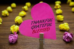 Text sign showing Thankful Grateful Blessed. Conceptual photo Appreciation gratitude good mood attitude Paperclip hold pink heart stock photos