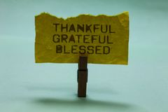 Text sign showing Thankful Grateful Blessed. Conceptual photo Appreciation gratitude good mood attitude Paperclip hold. Torn yellow page written brown words sky stock image