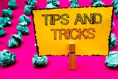 Text sign showing Tips And Tricks. Conceptual photo Suggestions to Make things easier Helpful Advices Solutions Clothespin hold ho. Lding yellow paper black red stock photo
