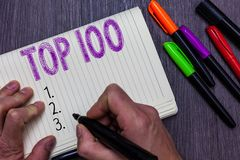 Text sign showing Top 100. Conceptual photo List of best products services Popular Bestseller Premium high rate Man. Holding marker notebook paper communicating royalty free stock photo