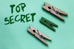 Text sign showing Top Secret. Conceptual photo telling someone important data or information that he cant tell Three brown green v. Intage clothespins clear stock image