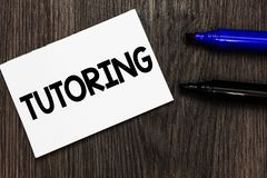 Text sign showing Tutoring. Conceptual photo An act of a person employed to administer knowledge to someone Important idea ideas n. Otebook marker markers wooden royalty free stock photo