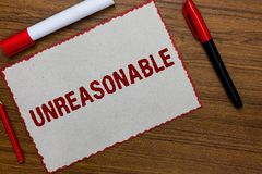 Text sign showing Unreasonable. Conceptual photo Beyond the limits of acceptability or fairness Inappropriate White paper red bord. Ers markers wooden background royalty free stock photos