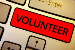 Text sign showing Volunteer. Conceptual photo Volunteering individual for greater social cause serving others Keyboard brown keys stock image
