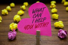 Text sign showing What Can I Help You With question. Conceptual photo Offering assistance Experts advice ideas Paperclip hold pink. Heart with text blurry paper royalty free stock images