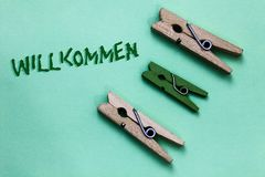 Text sign showing Willkommen. Conceptual photo welcoming people event or your home something to that effect Three brown green vint. Age clothespins clear royalty free stock photo