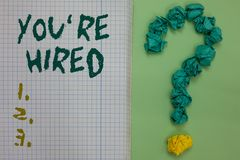 Text sign showing You re are Hired. Conceptual photo New Job Employed Newbie Enlisted Accepted Recruited Notebook paper crumpled p royalty free stock photos