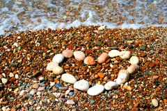 Text from small stones. Heart from small stones at sea background Stock Photo