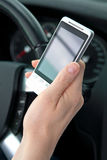 Text or SMS and drive. A young female's hand holding a smartphone while driving. Closeup image, focus on the phone Royalty Free Stock Image
