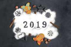2019 text made with flour with decorations on a black background. 2019 text, snowflakes  made with flour with decorations on a black background. Flat lay. Merry stock photography