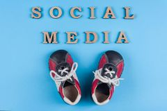 Text social media abstract wooden letters. Blue background with baby sneakers. People connecting and sharing social media.  stock photography