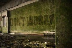 Text sorgen nicht sich auf der schmutzigen Wand in einem verlassenen ruinierten Haus Lizenzfreies Stockfoto