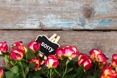 Text: sorry. Background with roses and chalkboard on wooden tabl. E. Top view with copy space Stock Photo