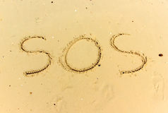 Text SOS on wet sand. Write by branch Stock Photos