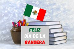 Text in Spanish: Happy day of the flag. Books with the flag of Mexico. Text in Spanish: Happy day of the flag. Books with the flag of Mexico stock images