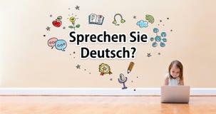 Text Sprechen Sie Deutsch mit dem kleinen Mädchen, das eine Laptop-Computer verwendet Lizenzfreie Stockfotografie