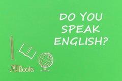 Text sprechen Sie Englisch, hölzerne Miniaturen des Schulbedarfs auf grünem Hintergrund stockfotos
