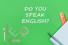 Text sprechen Sie Englisch, hölzerne Miniaturen des Schulbedarfs, Notizbuch auf grünem Hintergrund stockbild