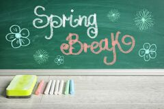 Free Text Spring Break And Flower Drawings On Green Chalkboard Near Wooden Table. School Holiday Royalty Free Stock Photo - 196649765