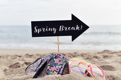Text spring break on the beach. Closeup of a black signboard in the shape of an arrow sign with the text spring break written in it and two pairs of colorful royalty free stock image