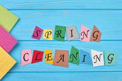 Text spring cleaning on wooden background. Kitchen cellulose napkins on blue wooden background. Time for spring clean up Royalty Free Stock Photo