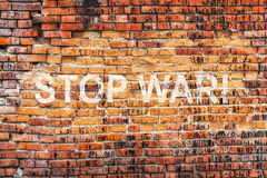 Text STOP WAR on stained old orange brick wall texture background Stock Photography