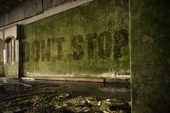 Text stoppen nicht auf der schmutzigen Wand in einem verlassenen ruinierten Haus Stockfoto