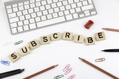 Text: SUBSCRIBE from wooden letters on white office desk stock photography