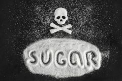 Text sugar and skull shape from sugar on black background, Concept royalty free stock photography