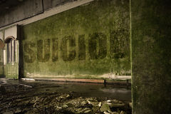 Text suicide on the dirty wall in an abandoned ruined house. Text suicide on the dirty old wall in an abandoned ruined house Stock Photography