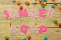 Text SUMMER CAMP of multicolored paper letters and candies on a natural wooden background. top view. flat lay royalty free stock image